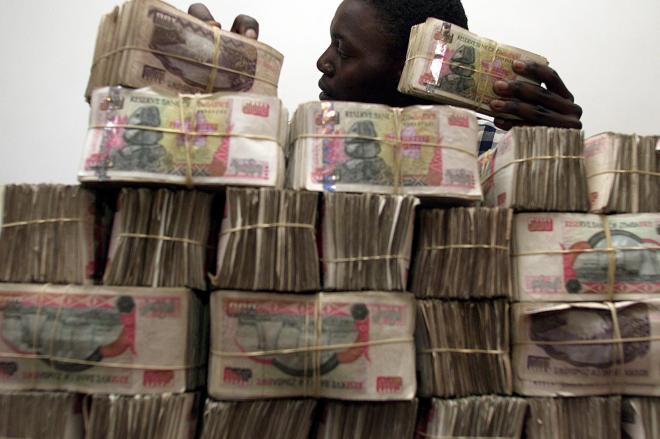 ジンバブエドルの札束を積み上げる両替商=2003年8月18日