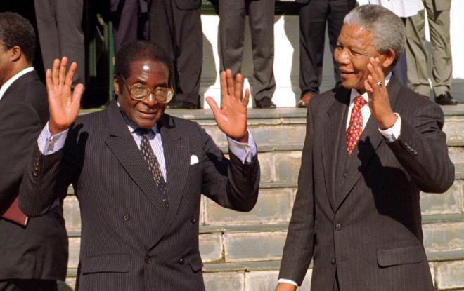 並んで手を振るムガベ氏とマンデラ氏(右)=1994年8月16日