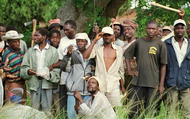 オノや短刀で武装する黒人グループ。このころ、黒人による白人の農場占拠が相次いだ=2000年8月9日