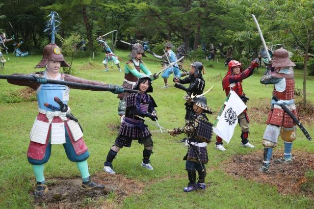 戦国武将たちの像が点在する中、甲冑姿で記念撮影する家族=2017年7月30日、岐阜県関ケ原町、吉本美奈子撮影