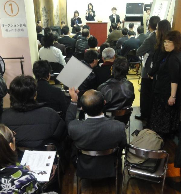 オークション会場からはみ出した席から、札を上げて骨董を競り落とす中国人男性=東京都中央区銀座、2010年12月6日