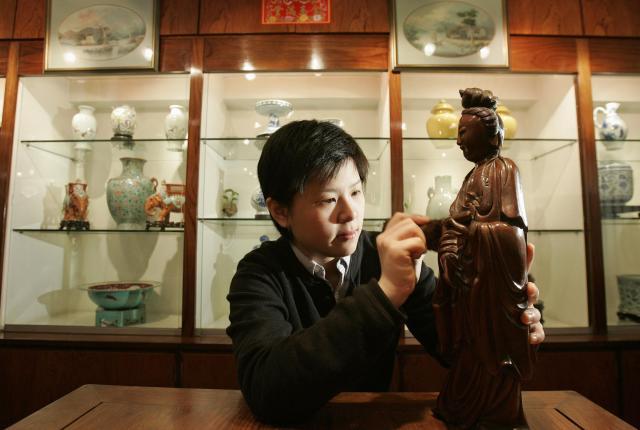 観音菩薩像を丁寧に掃除する骨董店の店員=2007年3月、香港