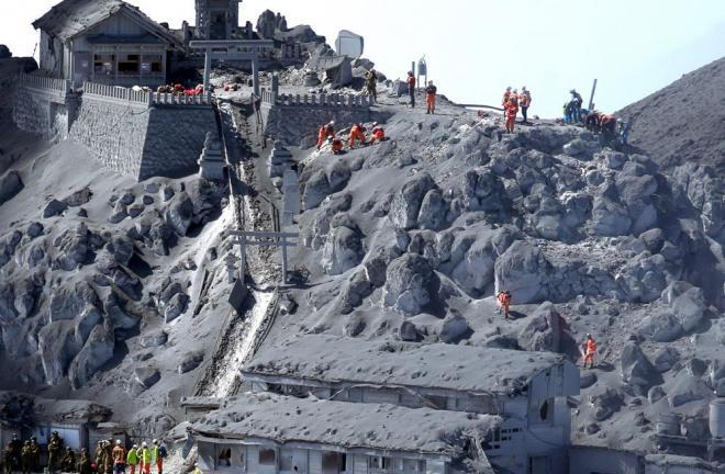 堀さんが撮影した御嶽山噴火翌日の山頂付近の写真。捜索活動が行われていた。左上が御嶽神社。御嶽頂上山荘(中央下)の屋根などが火山灰で覆われている=2014年9月28日午後0時56分、長野、岐阜県境