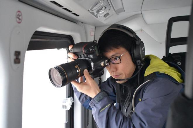 ヘリの中でカメラを構える加藤カメラマン