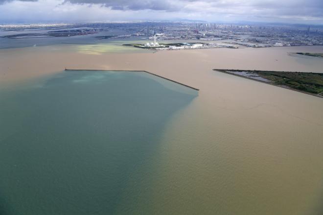 大和川から流れ込んだ土砂で大阪湾が茶色に染まる。堤防で遮られた部分は本来の海の色のままだった=10月23日午前、加藤諒撮影