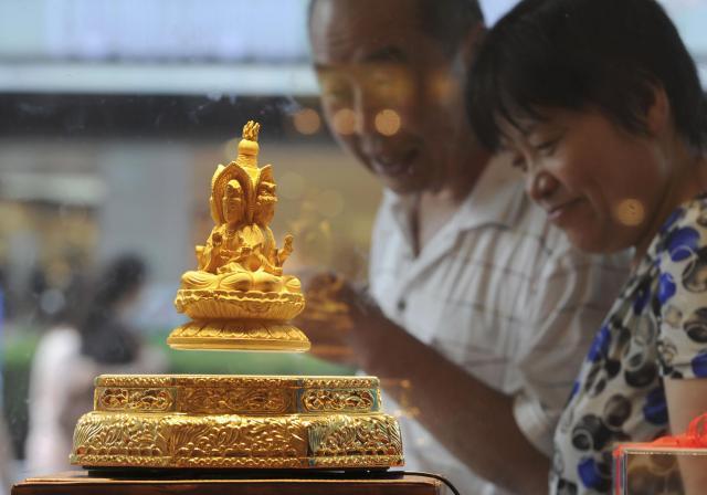 中国・安徽省合肥市のゴールドショップで、金の仏像を見つめる人々=2010年9月、