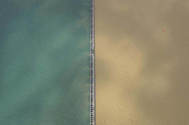 堤防を境にくっきりとツートーンに分かれた大阪湾=朝日新聞のヘリから、加藤諒撮影