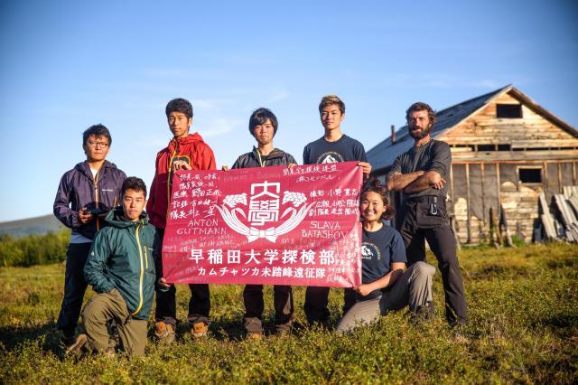 ベースキャンプの小屋の前で隊旗を掲げる早稲田大学探検部「カムチャツカ遠征隊」=2017年8月27日