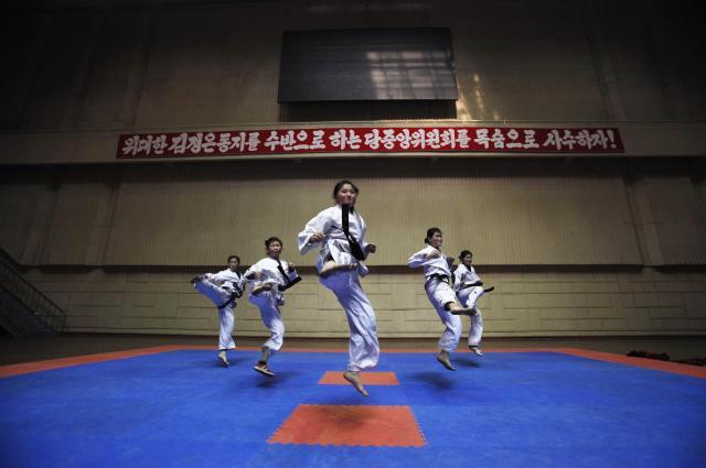 平壌でテコンドーを練習する女の子たち。後ろのバナーには励ましの言葉も書かれている=2012年4月、平壌、北朝鮮