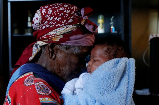 ズールー族の90歳のおばあちゃんが、ひ孫の世話をしている=2017年5月、南アフリカ