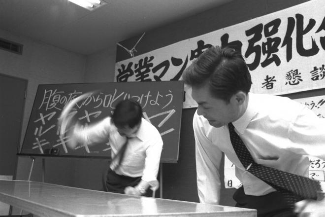 温泉旅館で太いゴムホースをたたき付け「やる気!やる気!」と叫ぶ社員(1969年9月)。高度成長時代はこうした「モーレツ社員」がたくさんいた。
