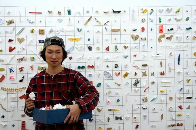 辰巳雄基さん。壁一面に展示された箸袋の造作物「JAPANESE TIP」を背に