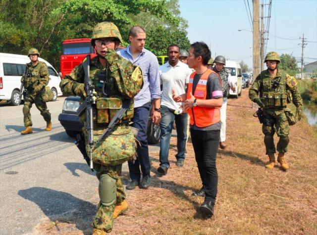 2月にタイであった多国間共同訓練で、陸自隊員に警護されながら空港へ向かう米国人ら=ウタパオ海軍航空基地