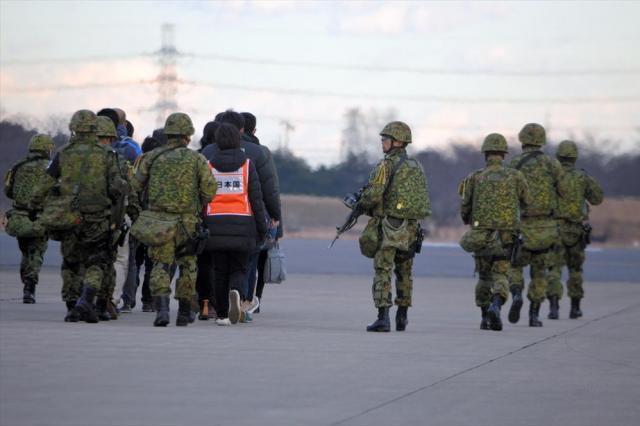 在外邦人役の人たちや外務省職員を囲んで滑走路を歩き、退避用の航空機へ誘導する陸自隊員ら=埼玉県狭山市の空自入間基地