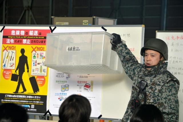 退避で乗り込む自衛隊の航空機に持ち込めないものなど、出国手続きを説明する役の空自隊員=埼玉県狭山市の空自入間基地