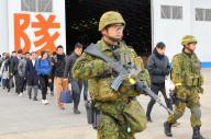 陸自隊員に守られながら退避のため滑走路の輸送機へ向かう在外邦人役の人たち=12月13日午後、埼玉県狭山市の空自入間基地