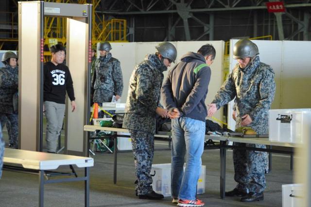 退避統制センターで金属探知機を通ったり、持ち物検査を受けたりする在外邦人役の人たち=埼玉県狭山市の空自入間基地