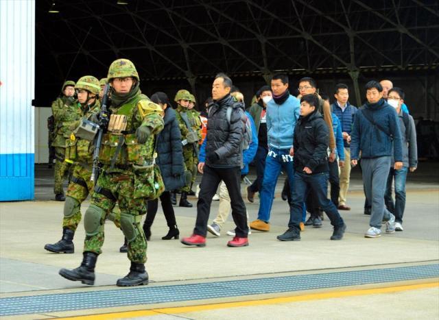 ライフルを持つ陸自隊員に守られながら歩く在外邦人役の人たち。滑走路で待つ退避用のヘリコプターへ向かう=埼玉県狭山市の空自入間基地