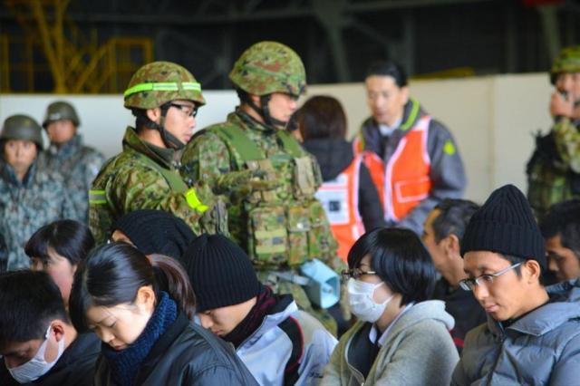 在外邦人役の人たち(手前)に、退避用の航空機まで滑走路を歩くときの注意事項を伝える陸自隊員ら=埼玉県狭山市の空自入間基地