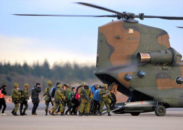 陸自隊員に守られながら退避のためCH47ヘリコプターに乗り込む在外邦人役の人たち=埼玉県狭山市の空自入間基地