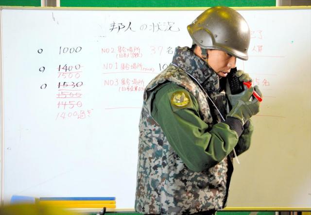 退避統制センターで在外邦人輸送の状況を確認しながらホワイトボードに書き込む役の陸自隊員=埼玉県狭山市の空自入間基地