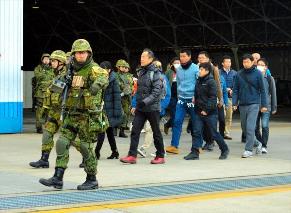 ライフルを持つ陸自隊員に守られながら歩く邦人役の人たち。滑走路で待つ退避用のヘリコプターへ向かう=12月13日午後、埼玉県狭山市の空自入間基地