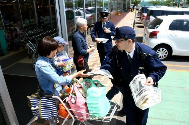 無防備な入山を自粛するよう呼びかける秋田県警の警察官=2017年5月20日、秋田市