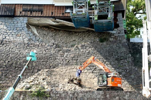 熊本城飯田丸五階櫓の崩れた石垣を撤去する無人の重機。左の高所作業車からリモートコントロールしている=2017年5月29日