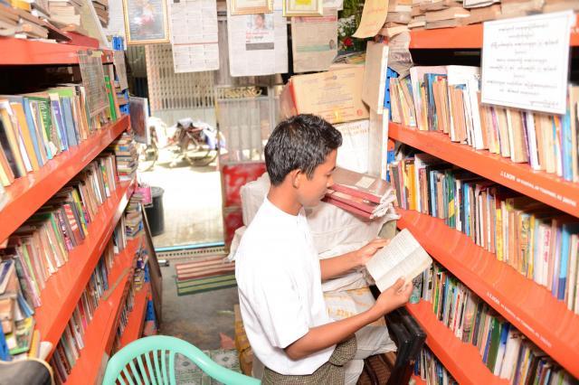 時には自分で図書館の本を読むことも。「同じ本でも毎回発見がある気がする」と話すゾーゾーさん=2017年10月、ミャンマー・ヤンゴン