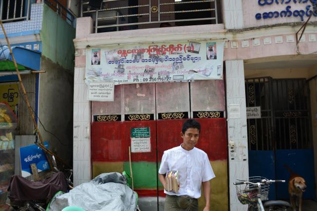本を持って「図書館」を出る、ゾーゾーさん。基本的に全て1人で取り仕切っている=2017年10月、ミャンマー・ヤンゴン