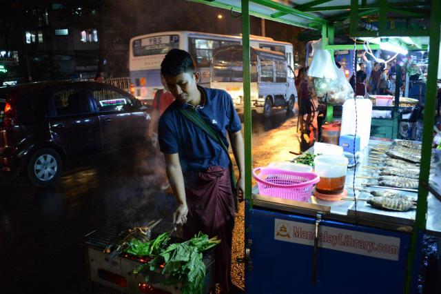 露店で魚や野菜を焼くゾーゾーさん。「じっくり火を通すことで魚が香ばしくなる」とか=2017年12月、ミャンマー・ヤンゴン
