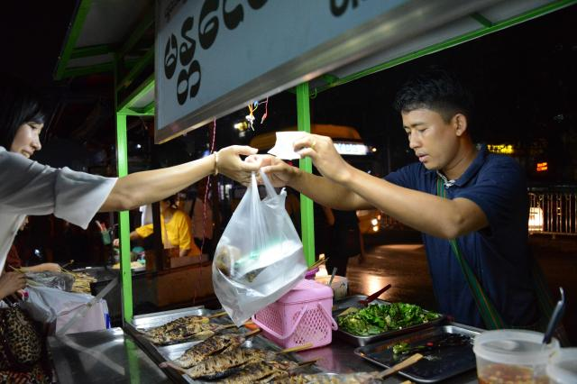 ゾーゾーさんの売る魚は人気。「おいしい」といううわさを聞きつけて買いにきて、「この人、テレビで見たことがある!」と驚いていた客もいた=2017年12月、ミャンマー・ヤンゴン