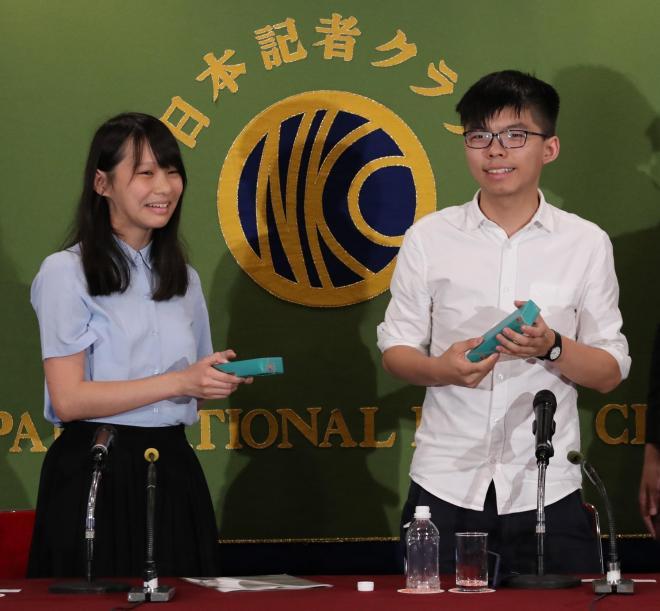日本記者クラブでの会見後に記念品を渡され、笑顔を見せるアグネス・チョウさん(左)とジョシュア・ウォンさん=2017年6月15日、東京都千代田区、細川卓撮影