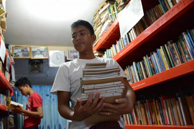 図書館の中には天井に届くくらいまで本が積み上げられている。ただ、「だいたいどの本がどこにあるかは頭に入っている」とゾーゾーさん=2017年10月、ミャンマー・ヤンゴン