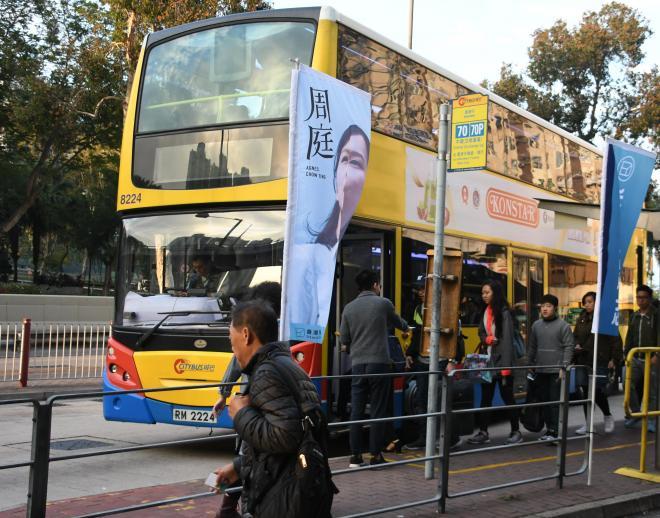 アグネスさんののぼりがはためくバス停。2階建てバスに通勤客らが乗り込んでいく=2017年12月15日、香港、益満雄一郎撮影