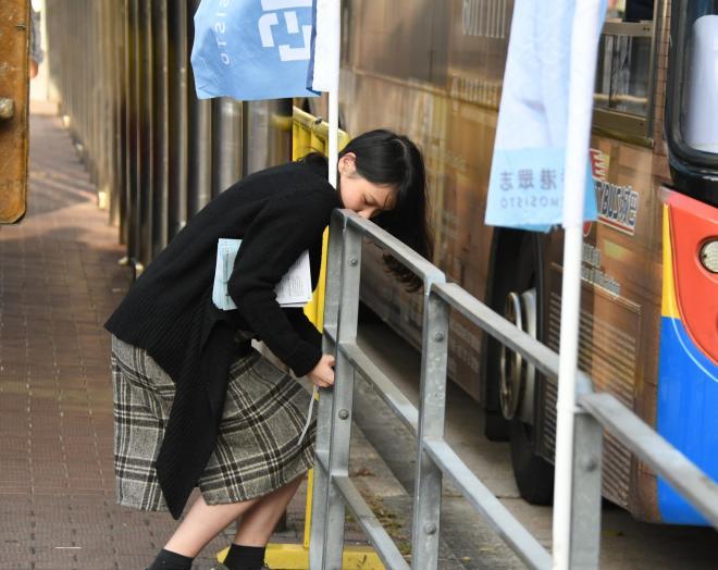 自身が所属する政党デモシストののぼりを固定するアグネス・チョウさん=2017年12月15日、香港、益満雄一郎撮影