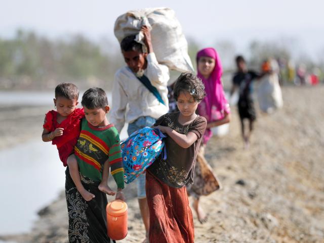 バングラデシュ南東部の国境の町テクナフで手に持てるだけの家財道具を担ぎ、ミャンマーから避難してくるロヒンギャの人たち=2017年11月20日、杉本康弘撮影