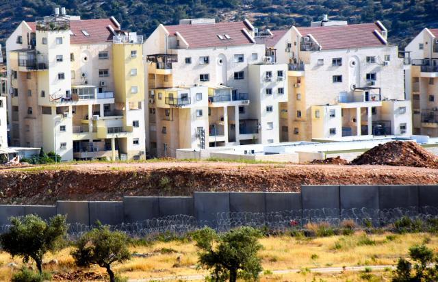 パレスチナ自治区のヨルダン川西岸ビリン村で、分離壁の向こうに広がるユダヤ人入植地=2017年6月