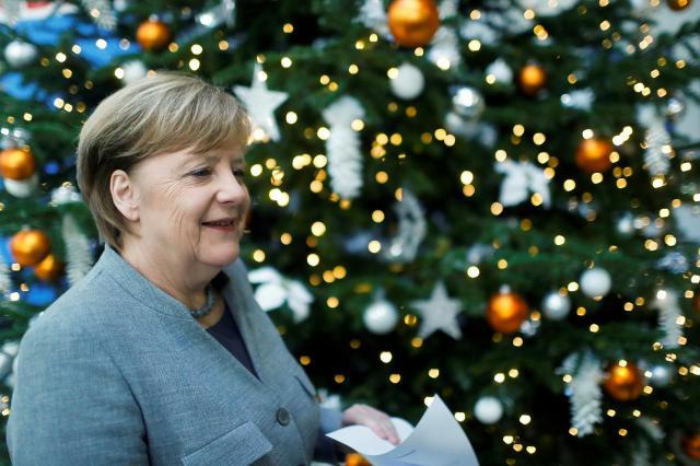 クリスマスツリーの前でほっと笑顔を見せたドイツのメルケル首相。2018年は良い年になるといいですね=2017年12月18日