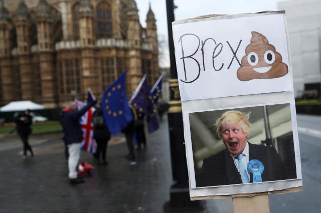 イギリスの国会前でEU離脱に反対するデモをする人たち。プラカードの写真はイギリスのボリス・ジョンソン外相=2017年12月13日