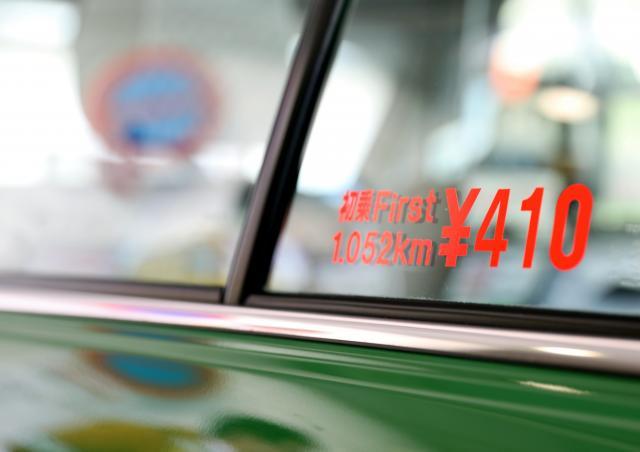 タクシーの車窓に掲示された、初乗り運賃410円の表示=2017年1月30日、都内