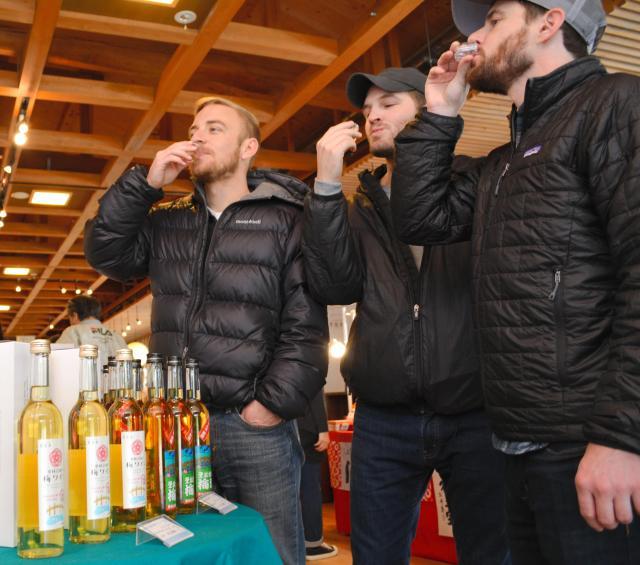 新発売された梅ワイン(手前)を試飲する外国人ゲスト=高松市