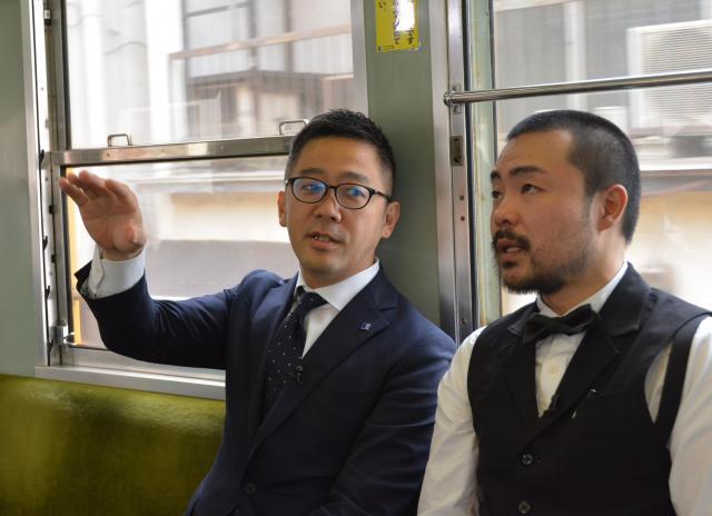 ことでん車内で語る真鍋さん(左)とマスターの岡田さん=高松市、田中志乃撮影