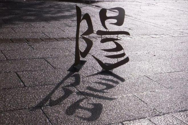 「陽」の文字の形をした彫刻に光を当てると、「陰」の文字が影として浮かぶ