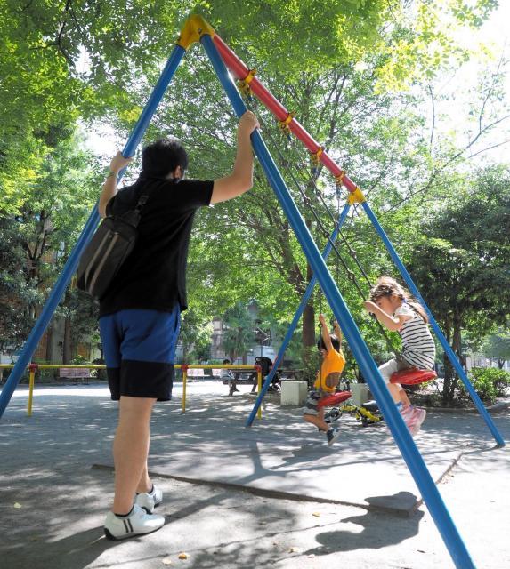 公園で遊ぶ子どもを見守る父親