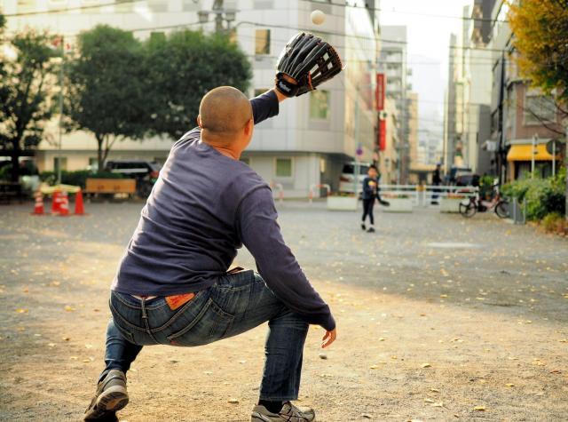 公園でキャッチボールをする父親