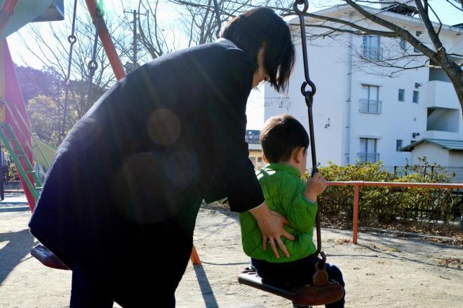 近所の公園で長男のブランコを押す真由美さん=福島県
