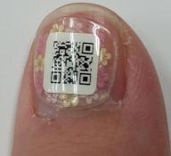 QRコードが印刷された小さなシールを貼った爪。認知症のお年寄りの連絡先が分かる