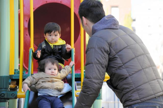 近所の公園で娘と遊ぶ父親。同じ年代の子どもがいることも多く、2時間ほどは付き合って走り回るという=東京都中央区