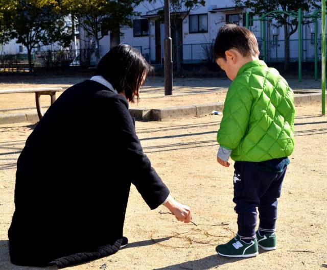 近所の公園で、長男の好きなキャラクターを木の棒で描く真由美さん=福島県